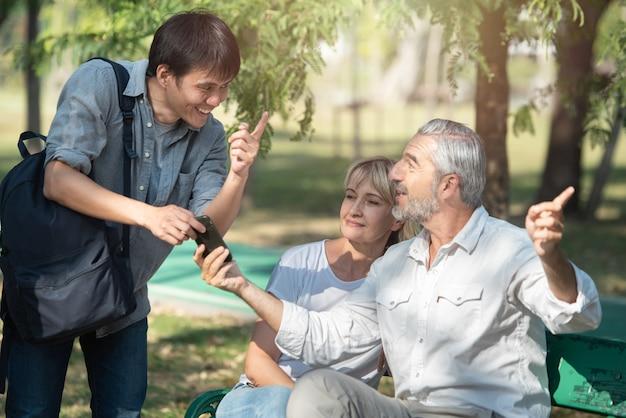 Aziatische toeristen jonge man met slimme mobiele telefoon in zijn handen vraagt om aanwijzingen van de oude blanke oudere man die bij de vrouw zit, hij wees met de vinger naar de weg.