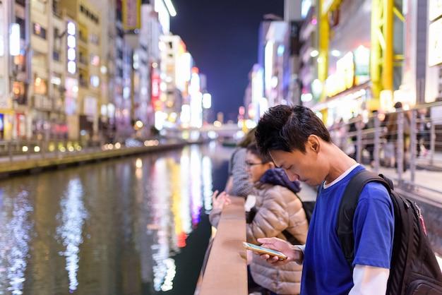 Aziatische toeristen man's kijkt zijn mobiele telefoon