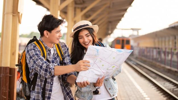 Aziatische toeristen met backpackas die een kaart gebruiken bij het station