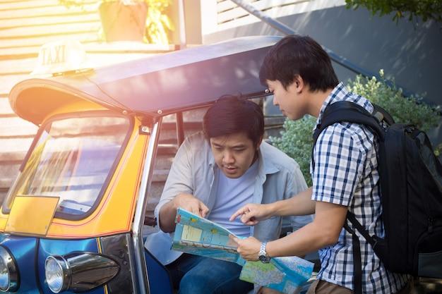 Aziatische toeristenfotograaf die manier met taxibestuurder of tuk tuk in thailand vragen