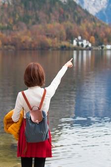 Aziatische toeristenreizigermeisje bevindende het richten vinger bij meer die vreedzame vrijheid voelen