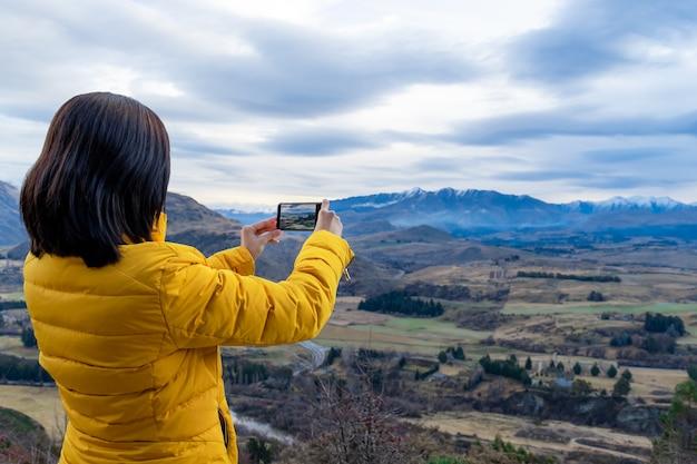 Aziatische toeristenvrouw die foto met mobiele telefoon in queenstown-zuidereiland nieuw-zeeland neemt