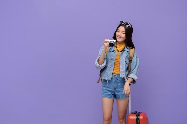 Aziatische toeristenvrouw die met bagage de camera bekijken