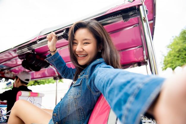 Aziatische toeristenvrouw die selfie op de taxi van tuk tuk in bangkok thailand nemen