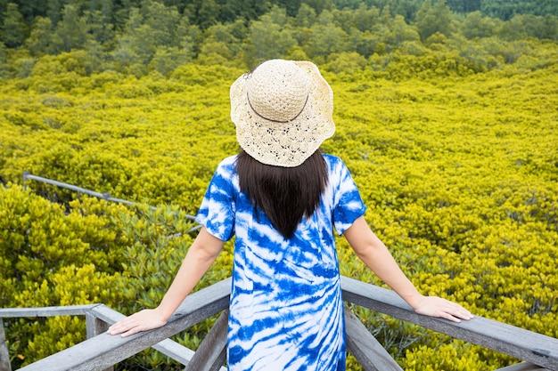 Aziatische toeristenvrouw die zich op tung prong thong mangrove forest boardwalk, thailand bevindt.