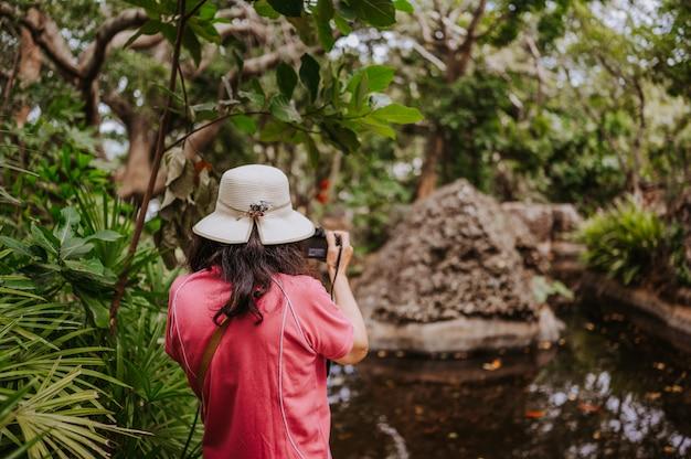 Aziatische toeristenvrouw in nationale hoed die foto's nemen bij natuurlijk groen park met tropische installaties en palmen. reizen azië toerisme