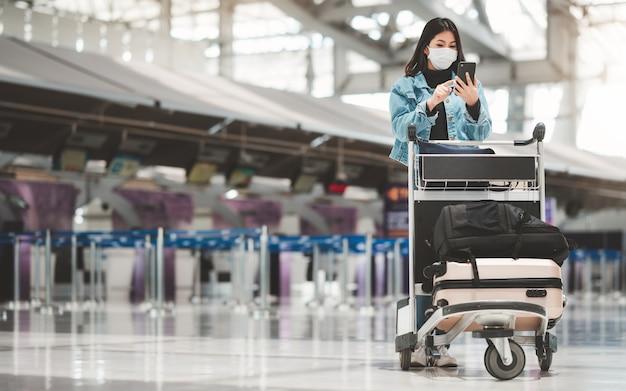 Aziatische toeristenvrouw met masker die mobiele telefoon met behulp van die zich met bagagekarretje bevinden