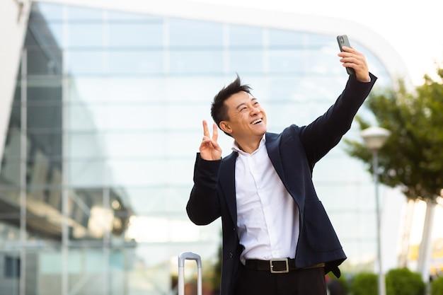 Aziatische toeristische zakenman aangekomen op een zakelijke conferentie maakt foto's in de buurt van de luchthaven en communiceert via video met collega's die een smartphone gebruiken
