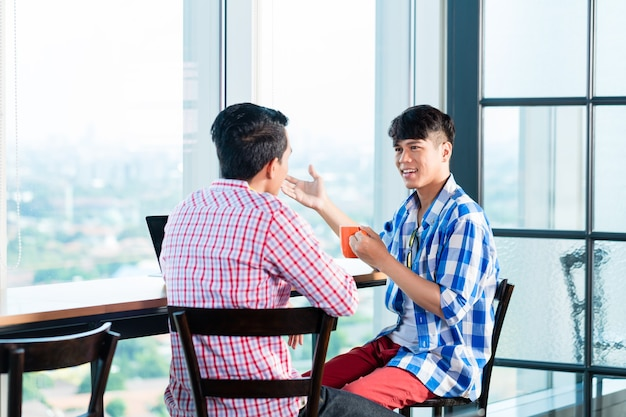 Aziatische toevallige bedrijfsmensen die in bureau bespreken
