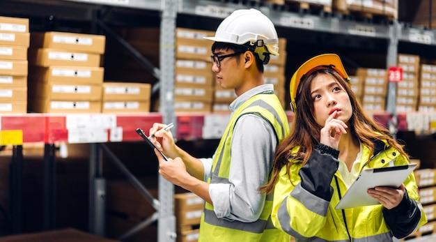 Aziatische twee ingenieur in helmen team bestellen details op tabletcomputer voor het controleren van goederen en benodigdheden op planken met goederen achtergrond in magazijn. logistieke en zakelijke export