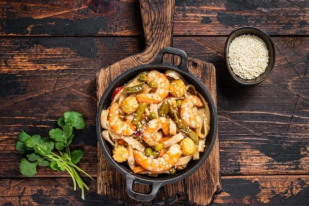 Aziatische udon roerbaknoedels met garnalen en garnalen in een pan