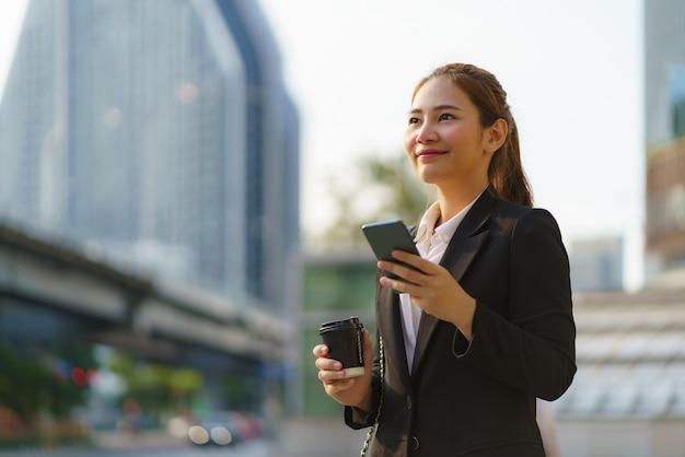 Aziatische uitvoerende werkende vrouw met koffiekopje en met behulp van een mobiele telefoon in de straat met kantoorgebouwen op de achtergrond in bangkok, thailand.