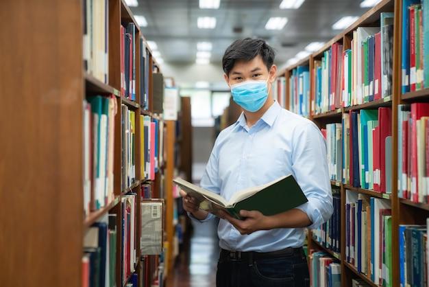 Aziatische universiteitsstudentjongen die gezichts beschermend medisch masker draagt voor bescherming