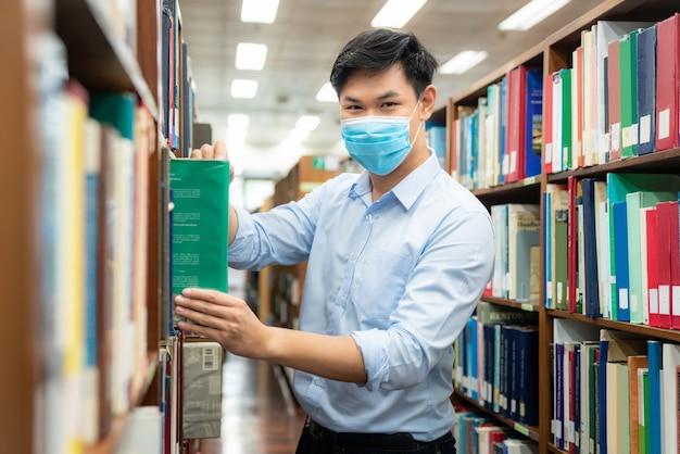 Aziatische universiteitsstudentjongen die medisch gezichtsbeschermend masker draagt voor bescherming tegen virusziekte