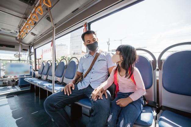 Aziatische vader brengt zijn dochter naar school met het openbaar vervoer per bus
