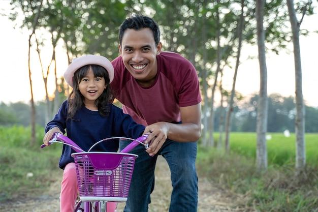 Aziatische vader die haar jong geitje helpt om openlucht fiets te berijden