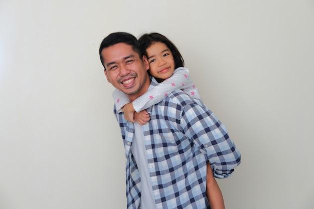 Aziatische vader die zijn dochter achterin draagt met een blije gezichtsuitdrukking