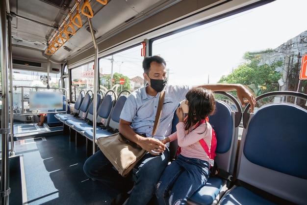 Aziatische vader die zijn dochter naar school brengt met het openbaar vervoer per bus met een gezichtsmasker op