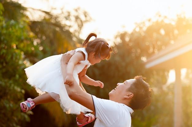 Aziatische vader die zijn dochter omhoog in de lucht vervoert en samen in het park speelt
