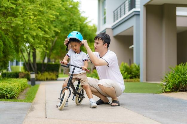 Aziatische vader draagt een helm voor zijn zoon terwijl hij zijn kind leert fietsen in een buurttuin, vaders hebben de hele dag contact met hun kinderen.