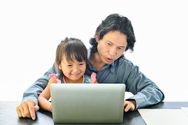 Aziatische vader en dochter die aan laptop op wit werken