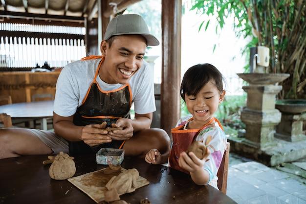 Aziatische vader en dochter die met klei werken