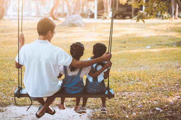 Aziatische vader en dochter die pret hebben om op schommeling samen in speelplaats bij het park te berijden