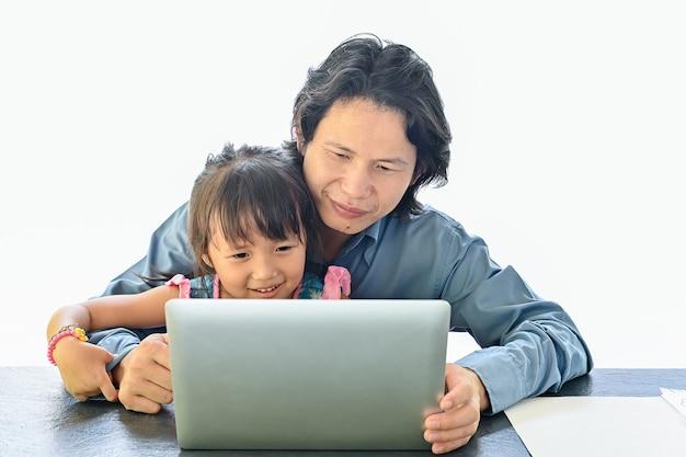Aziatische vader en dochter kijken op laptop scherm