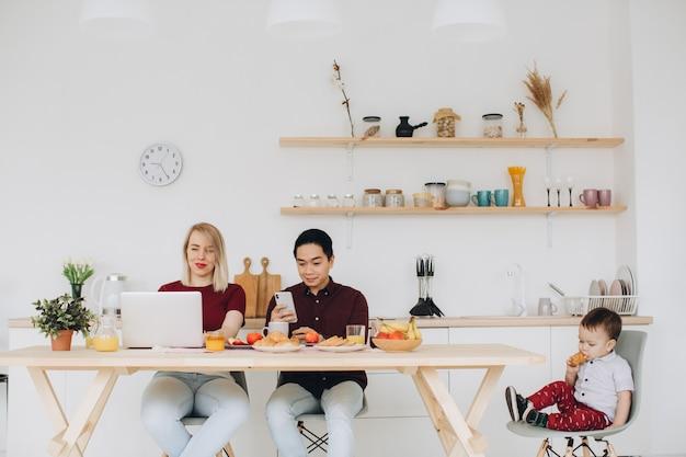 Aziatische vader en europese moeder werken met hun gadgets, en zoon ontbijt alleen. moderne technologische problemen.