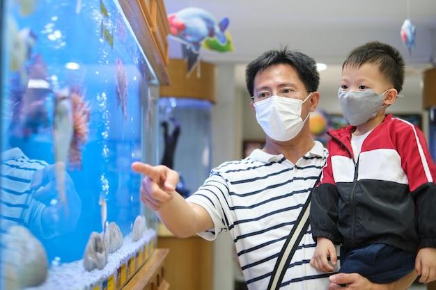 Aziatische vader en kind dragen van beschermende medische masker tijdens covid-19 uitbraak
