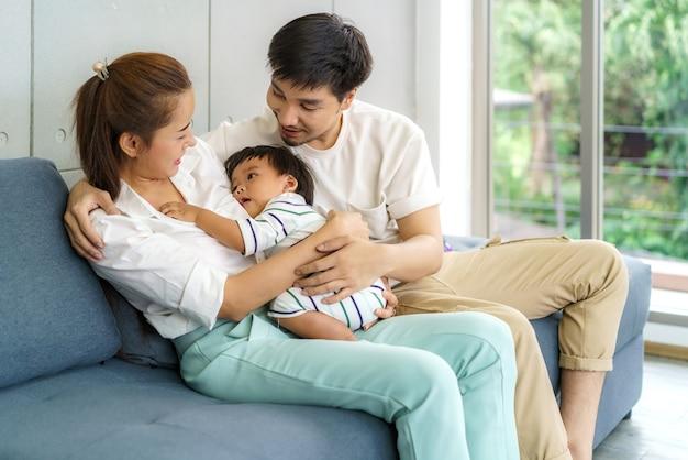 Aziatische vader en moeder knuffelen 9 maanden babyzoon op de bank. ze glimlachen en raken de baby warm aan met liefde in de huiskamer
