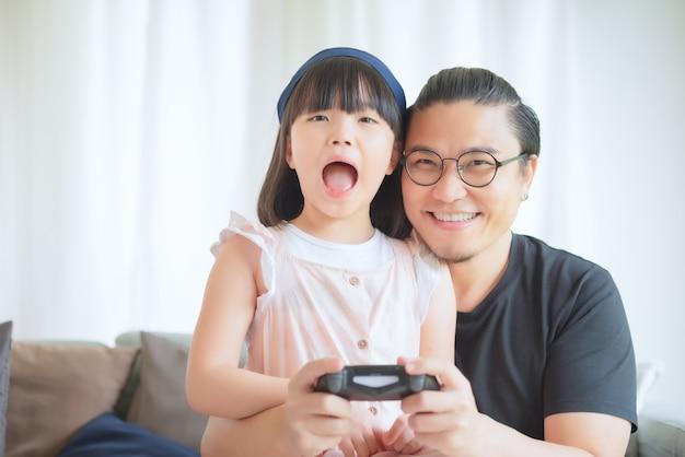Aziatische vader en schattige dochter genieten en spelen thuis op vakantie consolespel