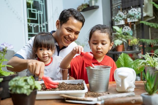 Aziatische vader en twee dochters zijn blij als ze een schep gebruiken om potplanten te kweken