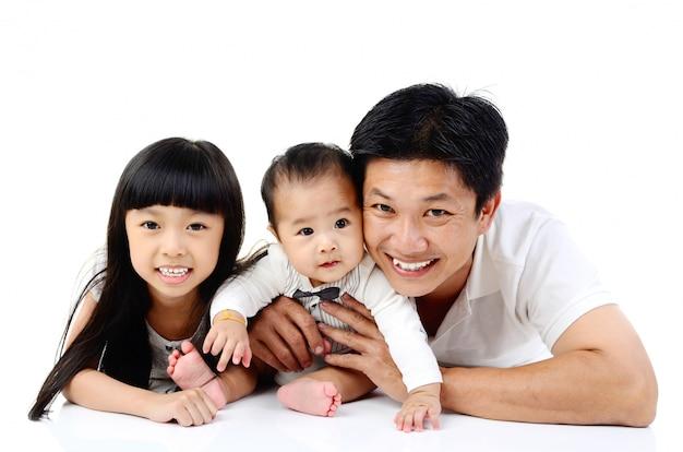 Aziatische vader en zijn schattige dochter en zoon die op de vloer liggen die op witte achtergrond wordt geïsoleerd.