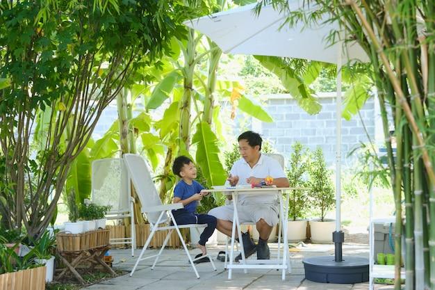 Aziatische vader en zoon hebben plezier bij het maken van eenvoudige diy stem-speelgoedboten voor studenten thuis