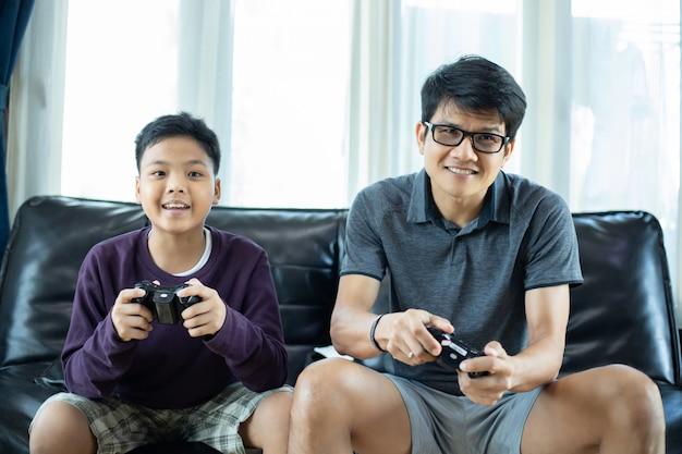Aziatische vader en zoon spelen graag videogames samen met video joystick met opwinding en erg leuk in de woonkamer thuis
