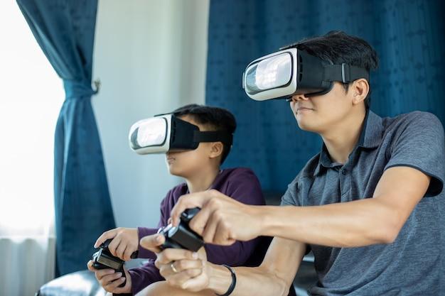 Aziatische vader en zoon spelen graag videogames samen met videobedieningshendel en virtual reality-bril met opwindend en erg leuk in de woonkamer thuis