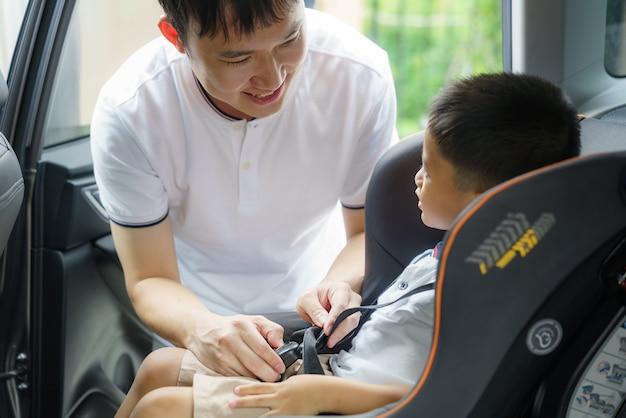 Aziatische vader klikt kind in autostoeltje tijdens het reizen, vaders hebben de hele dag contact met hun kinderen.