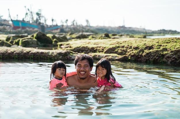 Aziatische vader knuffels zijn twee dochters tijdens het zwemmen op het strand