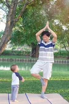 Aziatische vader met gesloten ogen en 1 jaar oude peuter jongen kind praktijken yoga & mediteren buiten op de natuur in de zomer, gezonde levensstijl concept