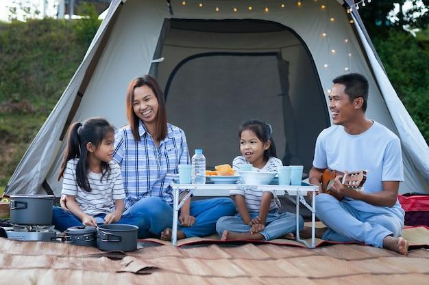 Aziatische vader, moeder en twee kindmeisjes die plezier hebben om buiten de tent te picknicken op de camping in de prachtige natuur.