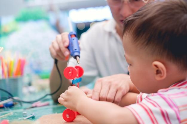 Aziatische vader onderwijs kind maken auto speelgoed met gerecyclede materialen.