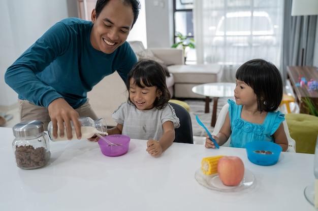 Aziatische vader ontbijten met zijn twee kleine meisjes