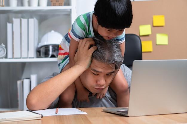 Aziatische vader probeert op het kantoor aan huis te werken met een laptop met een dochter die in chaos is geraakt