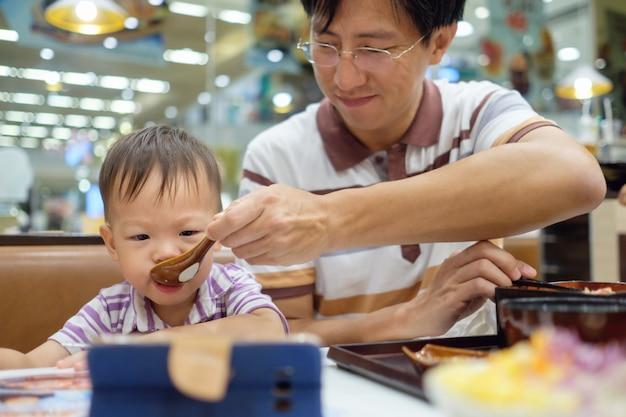 Aziatische vader voederen van voedsel aan schattige kleine aziatische 2 jaar oude peuter jongenskind tijdens het kijken naar smartphone in restaurant, peuters en eten manieren, vrije tijd & internetverslaving concept