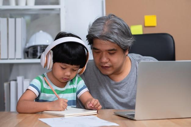Aziatische vader werkt thuis met een dochter en studeert online en leert samen van school.
