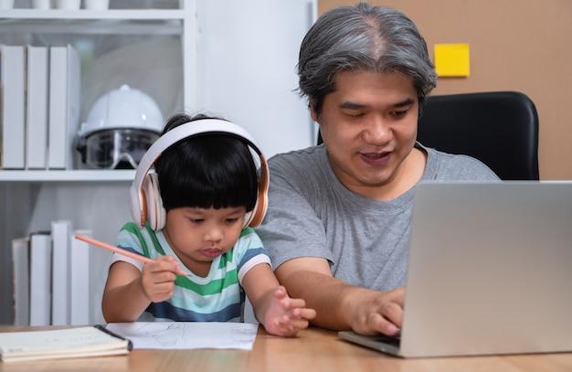 Aziatische vader werkt thuis met een dochter en studeert online en leert samen van school
