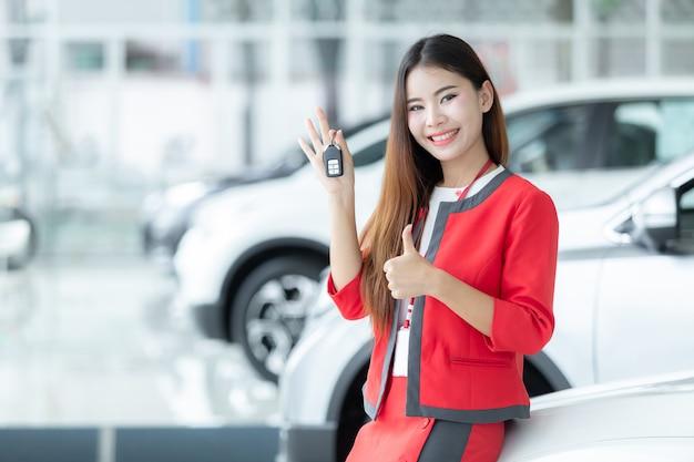 Aziatische verkoopster die autosleutel over autoshowachtergrond, autobusiness, autoverkoop geeft.