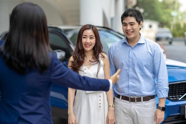 Aziatische verkoopster die de paarklant welkom heten bij het controleren van de auto voor toonzaal