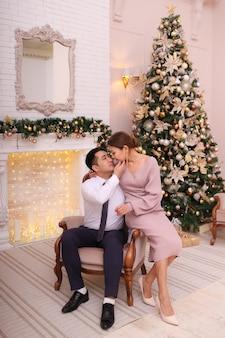 Aziatische verliefde paar in elegante outfits vieren kerstmis bij de open haard en boom in luxehuis Premium Foto